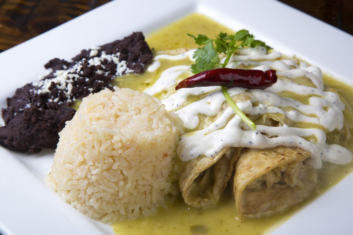 Two Enchiladas verde sit atop a white square plate drizzled with chipotle cream and verde sauce. A cylindrical-shaped stack of Mexican rice sits beside the enchiladas with a dollop of refried beans behind it.