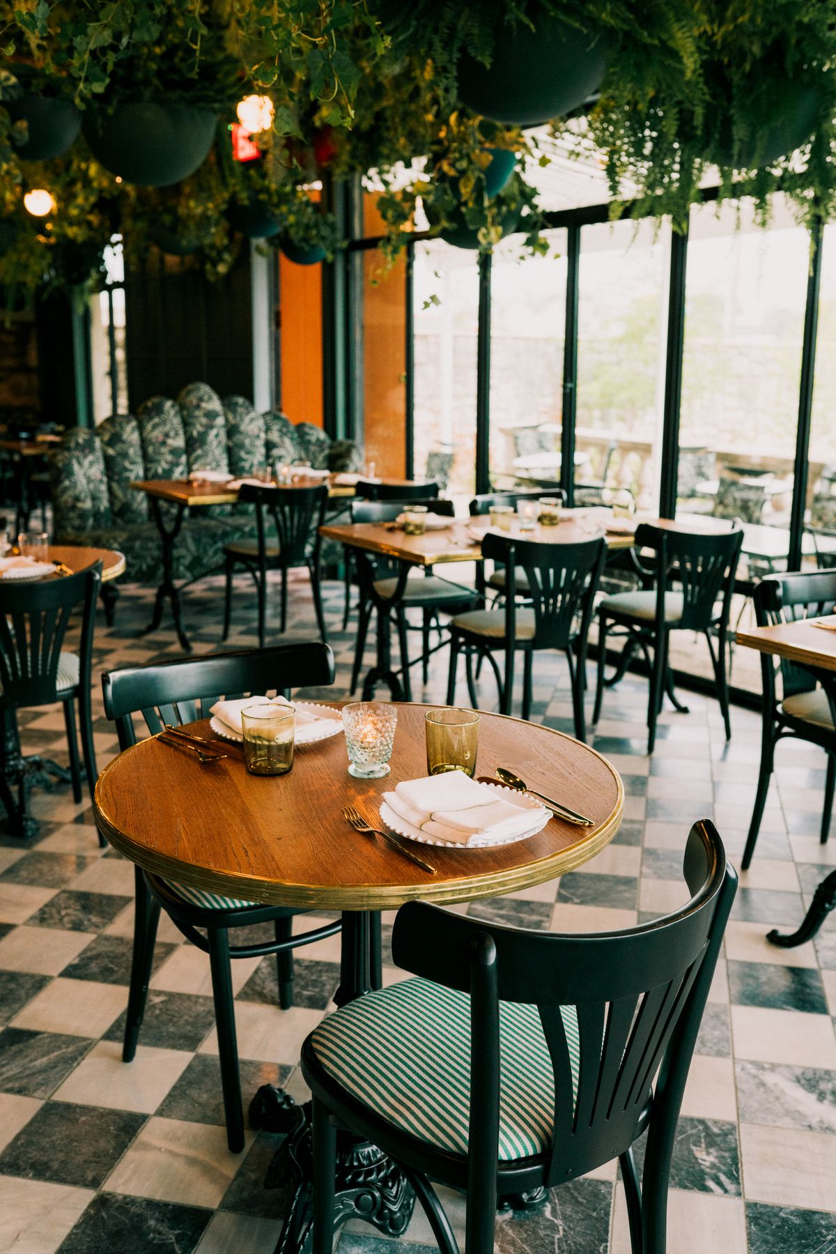 A vertical photo of tables and chairs in the main dining room surrounded by a canopy of greenery and bright natural light from a row of window.