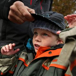 Todd Jr. Dickerman tries on hats at the 10th annual Community Coat Exchange at Pioneer Park in Salt Lake City on Friday, Nov. 28, 2014.