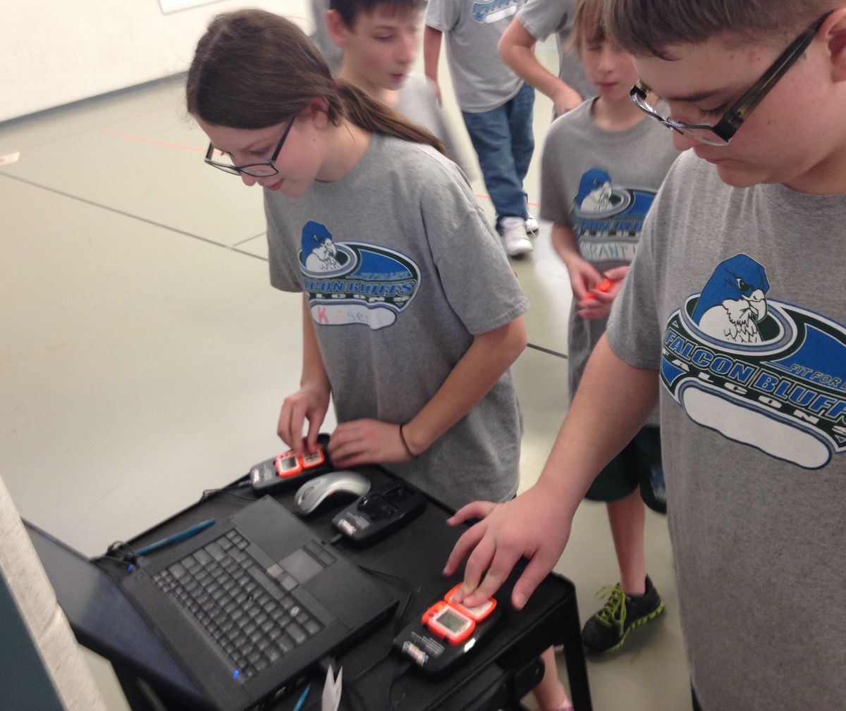 Two students in Allyn Atadero's P.E. class plug their pedometers into docking stations after class so their MVPA numbers will be recorded.