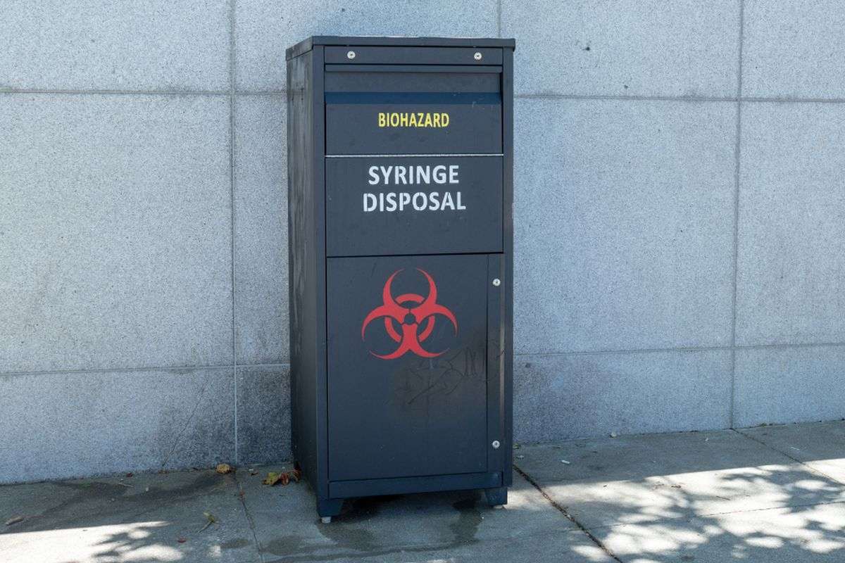 """A black metal box on a sidewalk with the words """"syringe disposal"""" written on the side."""