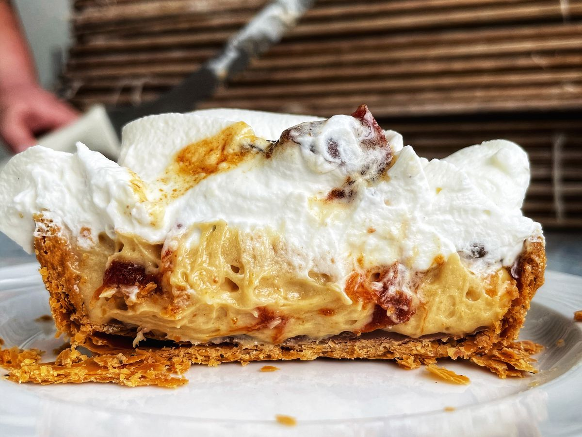 A piece of pie on a plate sliced sideways to reveal gooey peanut butter filling, hefty whipped topping, crumbly crust, and scattered toppings