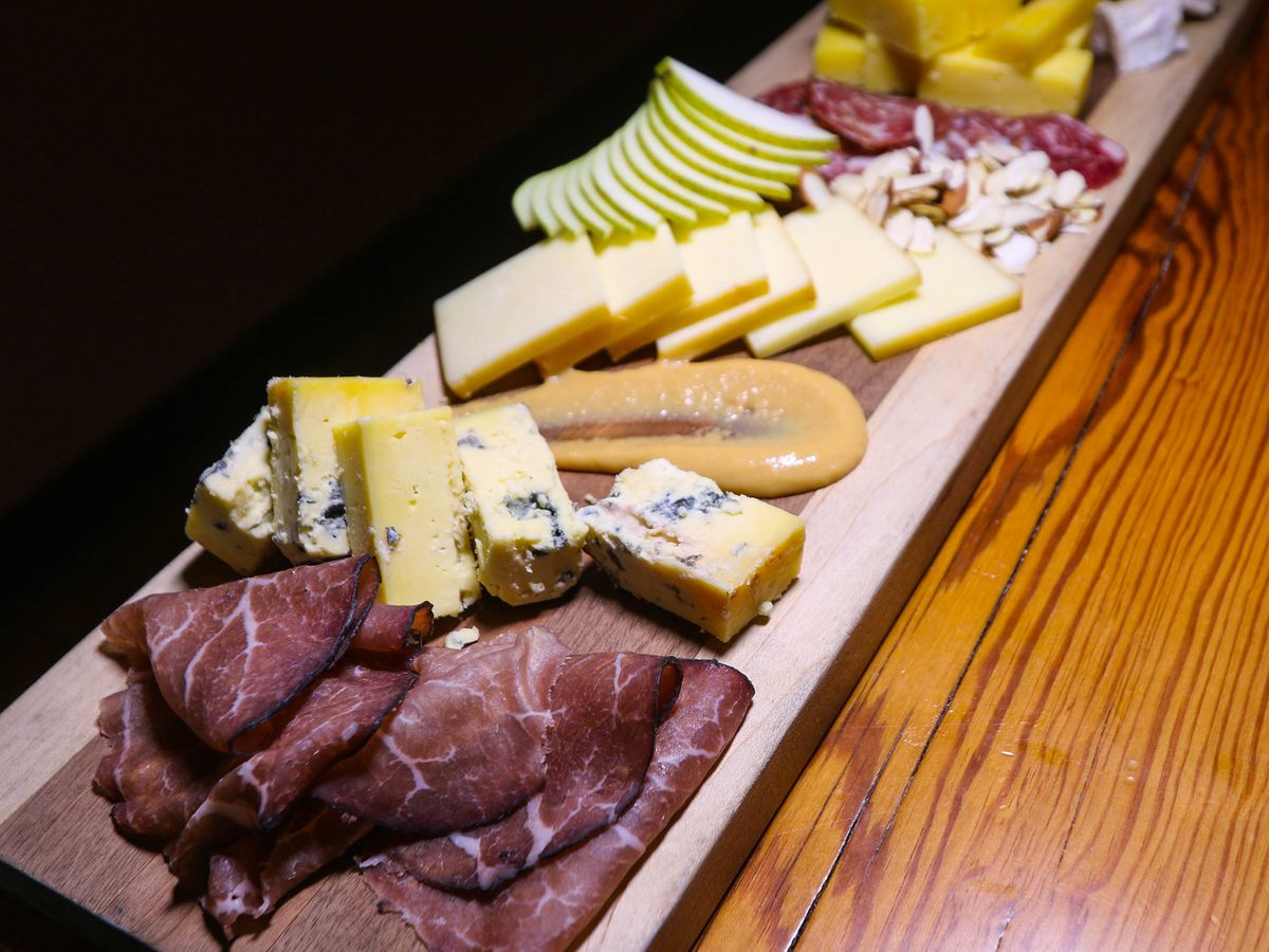 A wooden board, sitting on a wooden table, is coming toward the foreground of the photo at an angle. It is covered with cheese and charcuterie.