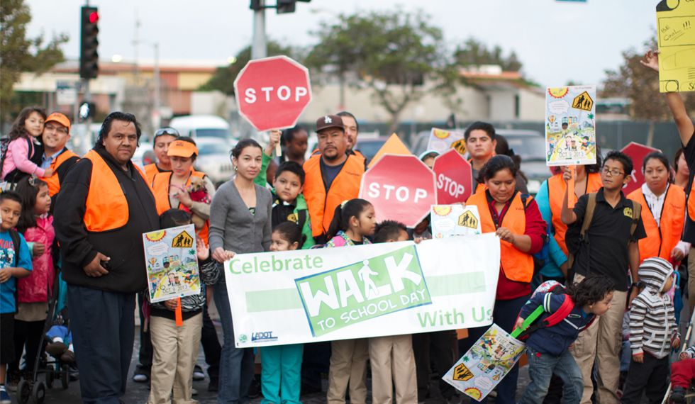 """A large group of students, teachers, and parents wearing safety vests are holding homemade stop signs and a large banner reading """"Celebrate Walk to School Day With Us."""""""