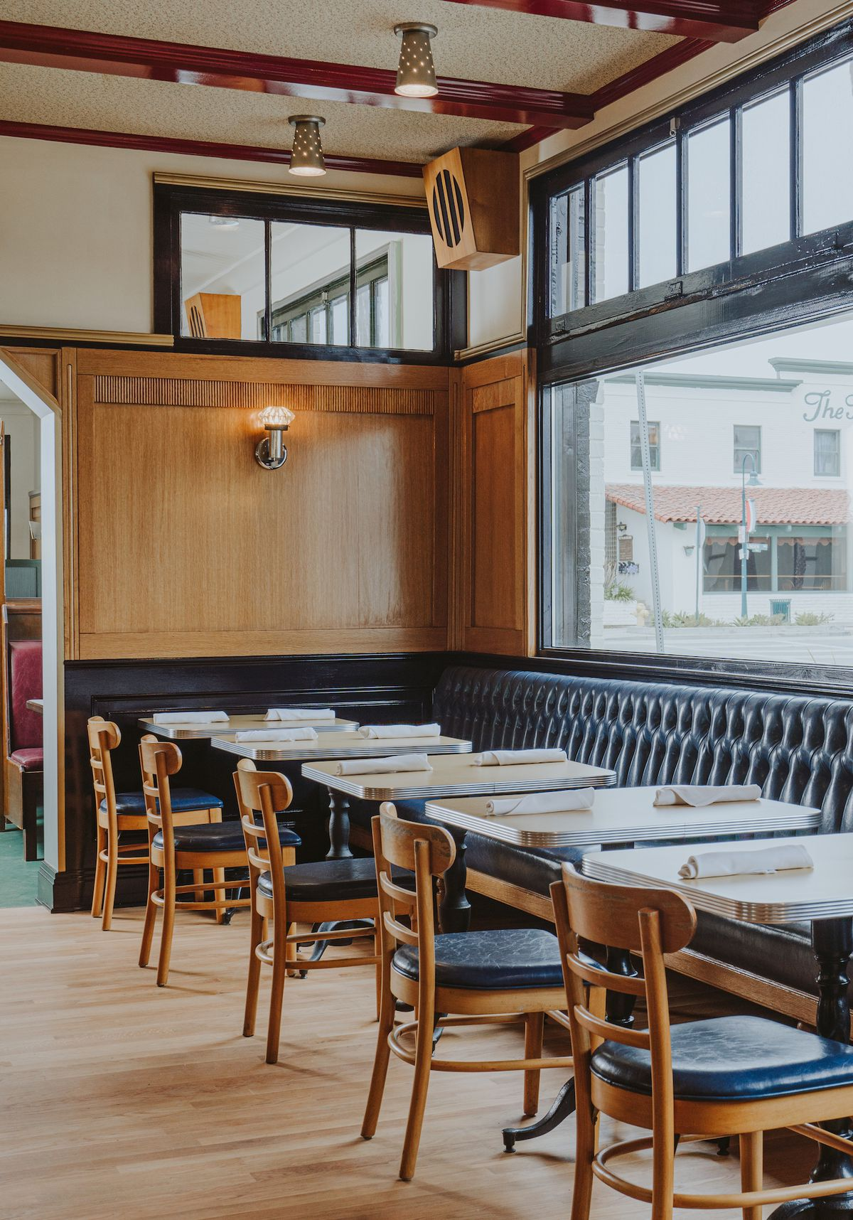 A tall restaurant dining room with a black banquette and lots of wood.