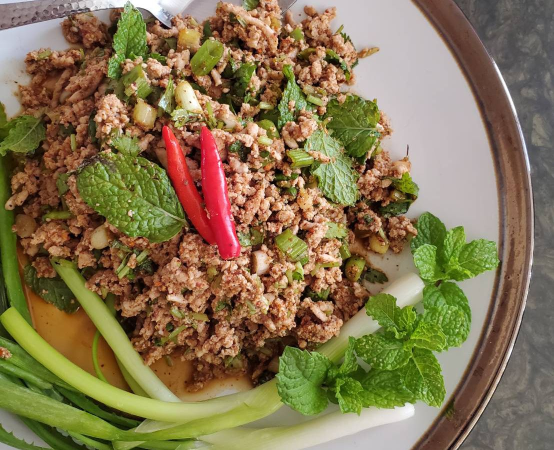 A plate of larb garnished with mint, chilies, and green onions at Sovereign Thai.