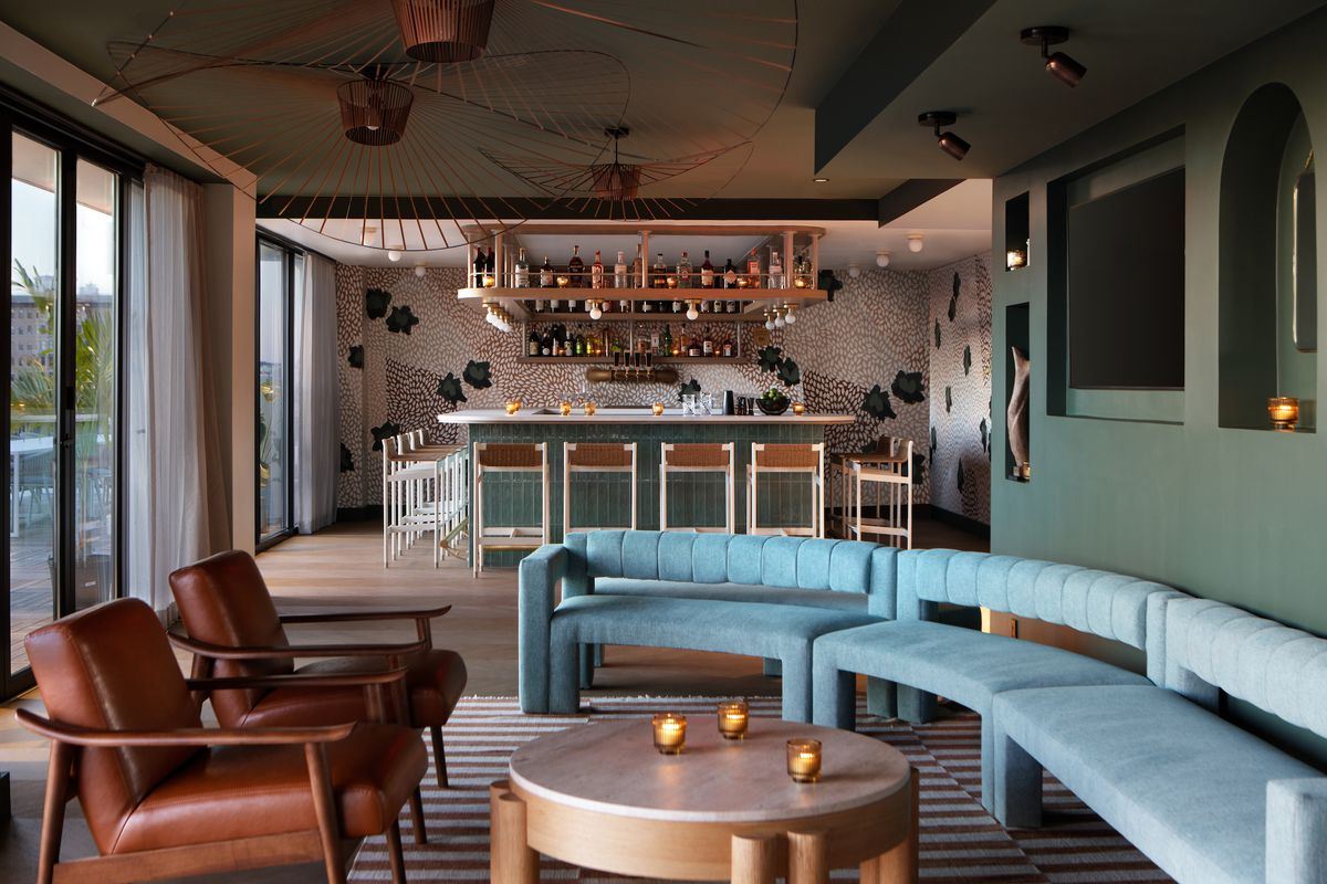 Lady Bird's bar is framed with hand painted wallpaper, teal tones, and metallic light fixtures.