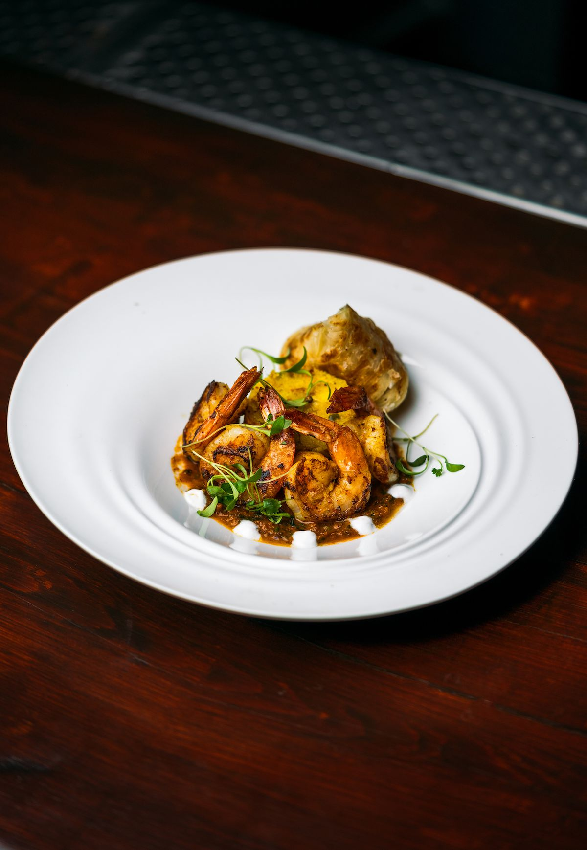 A white plate on a wooden table. The late has a couple of pieces of cooked shrimp, some rice, and some greens sprinkled on top