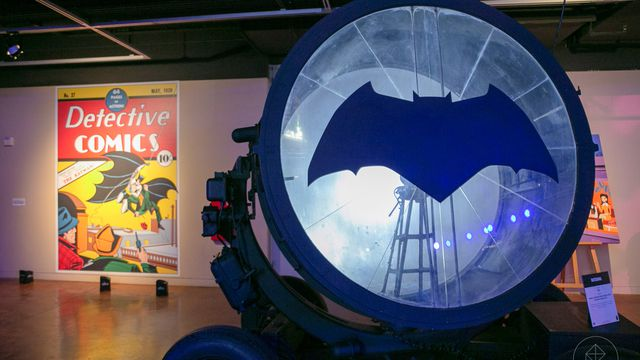 Bat Signal, used in one of the Batman movies, beside a large poster of the cover of Detective Comics #27 at San Diego Comic-Con