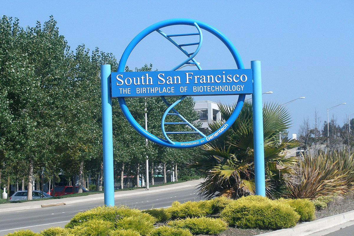 A circular blue sign welcoming people to South San Francisco.