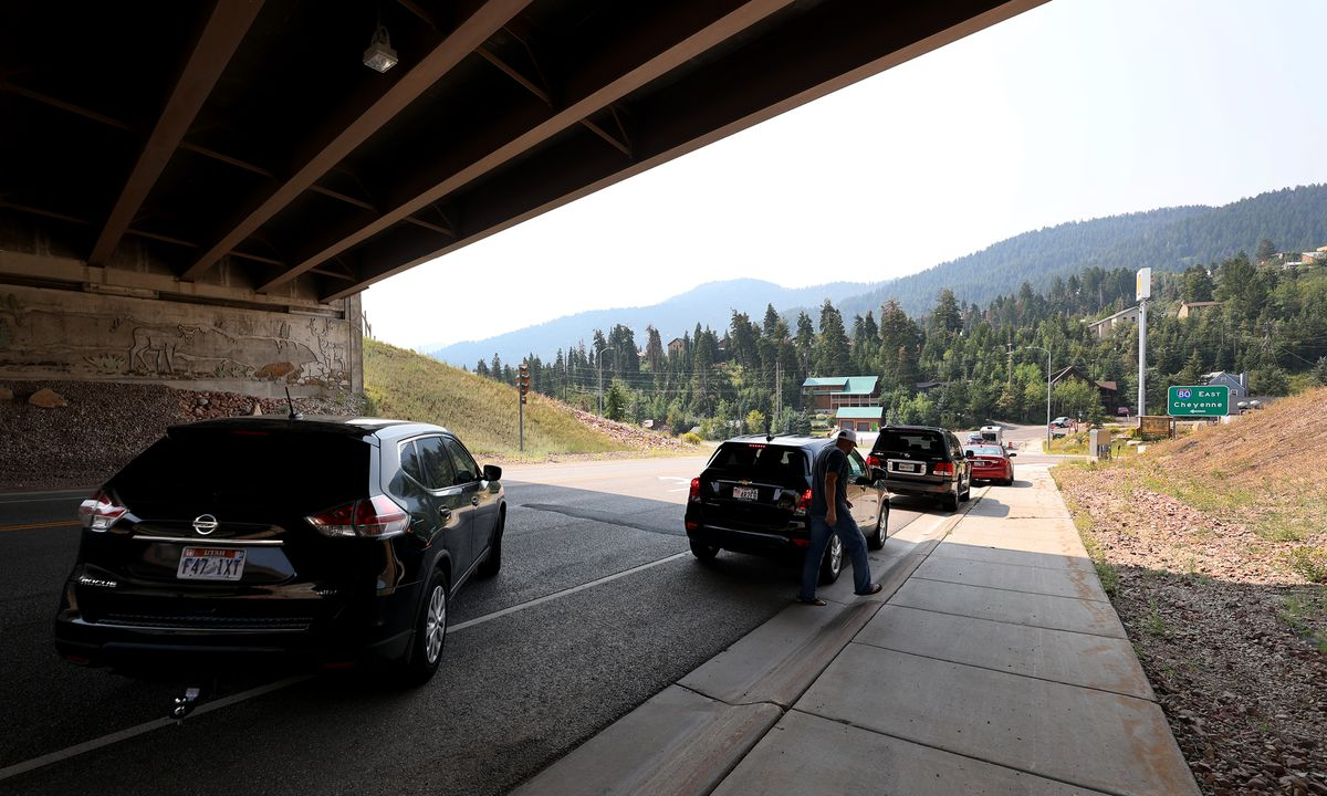 A few residents wait in the shade of an overpass waiting to get into Summit Park as crews fight the Parley's Canyon Fire near Park City on Monday, Aug. 16, 2021.