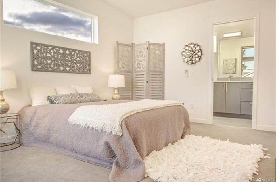 A white bedroom in a master suite. A door leads to a bathroom.