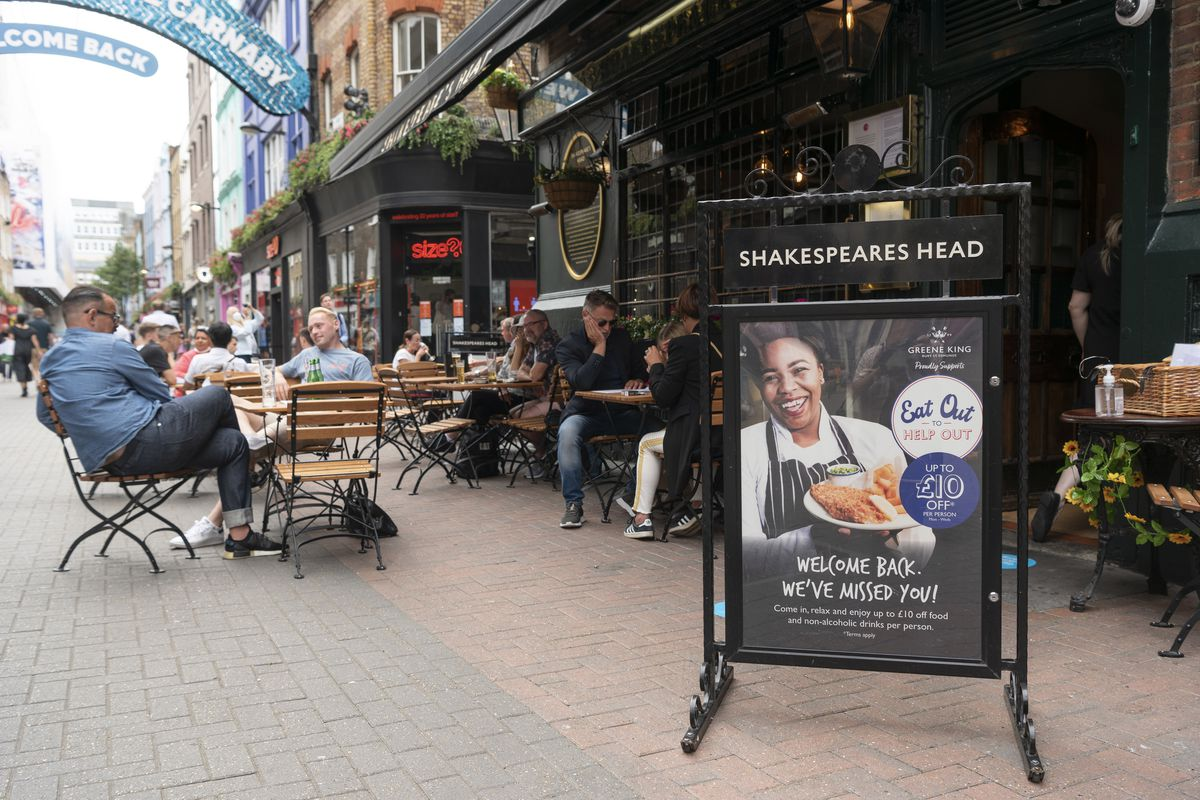 Diners sit on a patio outside a restaurant in London