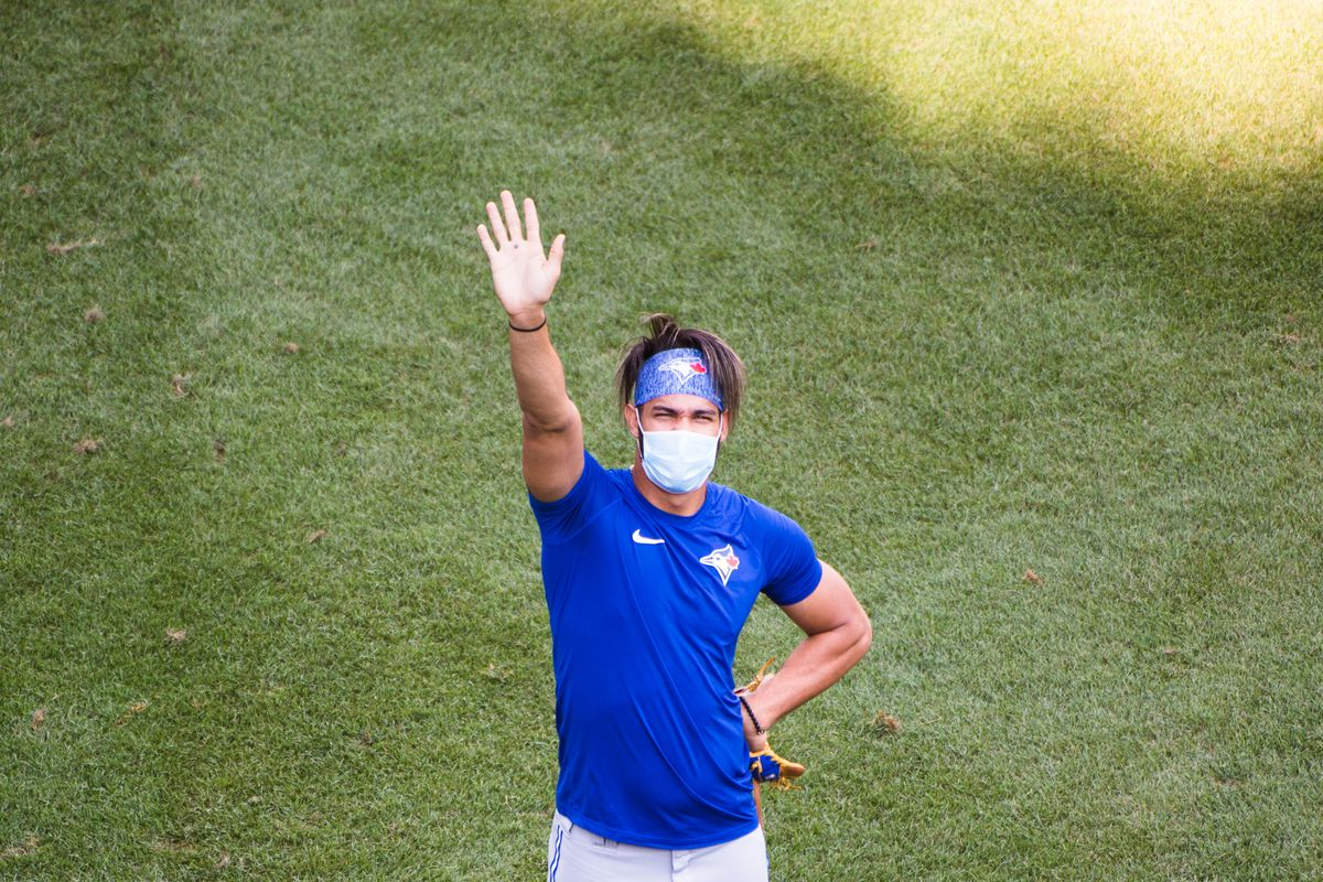 A masked Lourdes Gurriel waves to the camera during the Blue Jays' batting practice prior to the start of an exhibition game against the Red Sox at Fenway Park.