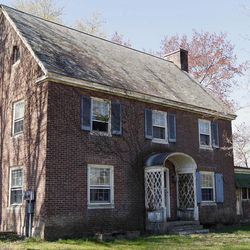 This April 4, 2012, photo shows a house that was used as a staff residence on the grounds of Coxsackie Correctional Facility in Coxsackie, N.Y. Coxsackie Correctional, which initially opened in 1935 as a reformatory for juveniles, has the vacant superintendent's house on the sprawling grounds and two staff residences occupied by correction officers. The stately brick house once occupied by the superintendent of New York's oldest prison will soon go on the real estate market in central New York. With eight bedrooms, six baths, an attached gazebo and a detached barn-size garage, the three-story house affiliated with Auburn Correctional Facility is appraised at $366,500.