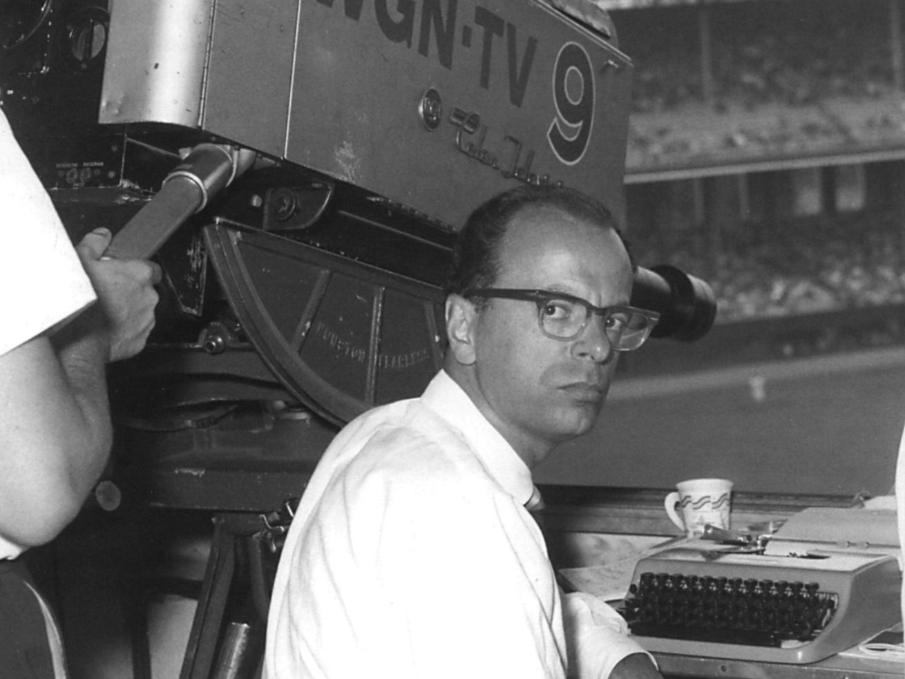 Former WGN sports editor Jack Rosenberg, shown in a 1958 photo at Comiskey Park, has died at age 94.