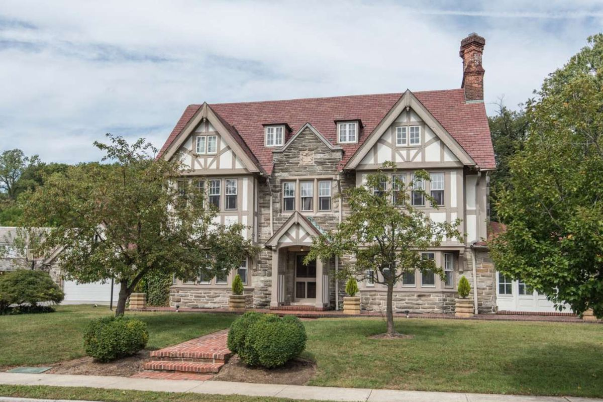 A large Tudor on a well-manicured green lawn.