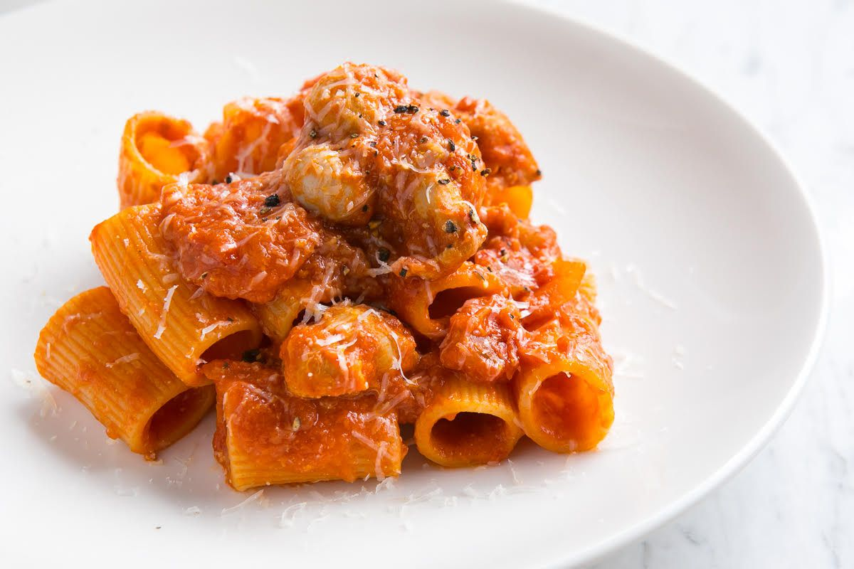 A stack of rigatoni with sauce and meat on a white plate