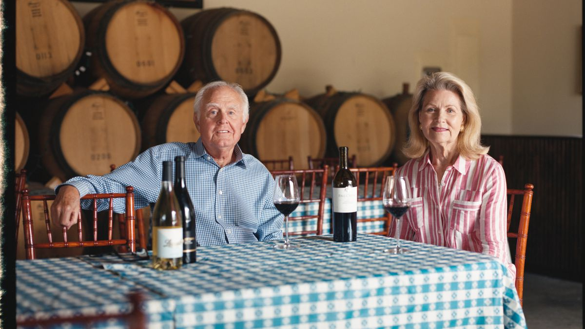 An older man in a blue-check button-down shirt seated at a table with a blue-patterned tablecloth holding a glass of red wine with an older woman in a pink-and-white vertically striped button-down shirt with a wine glass in front of her, and there are wine bottles on the table and wine barrels behind them.