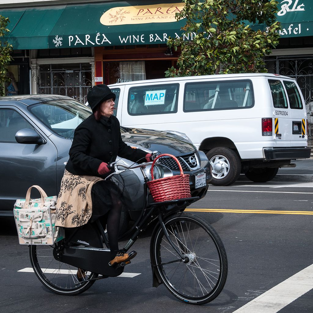A woman riding her bicycle amidst traffic on a street in San Francisco.