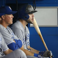 Mike Moustakas #8 of the Kansas City Royals gets ready to bat from the dugout as manager Ned Yost #8 looks on during MLB game action against the Toronto Blue Jays on August 31, 2013 at Rogers Centre in Toronto, Ontario, Canada.
