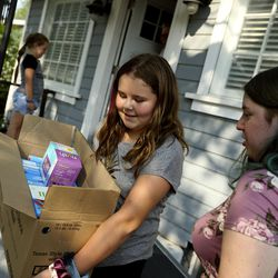 Kentlie Babwright and her sisters get boxes of food from their neighbor, Jerry Dolejs, after his visit to the Utah Food Bank mobile pantry at The Church of Jesus Christ of Latter-day Saints' Cannon Stake Center in Salt Lake City on Wednesday, Sept. 1, 2021. Dolejs keeps a few items for himself and gives the majority of the food to the Babwright family.