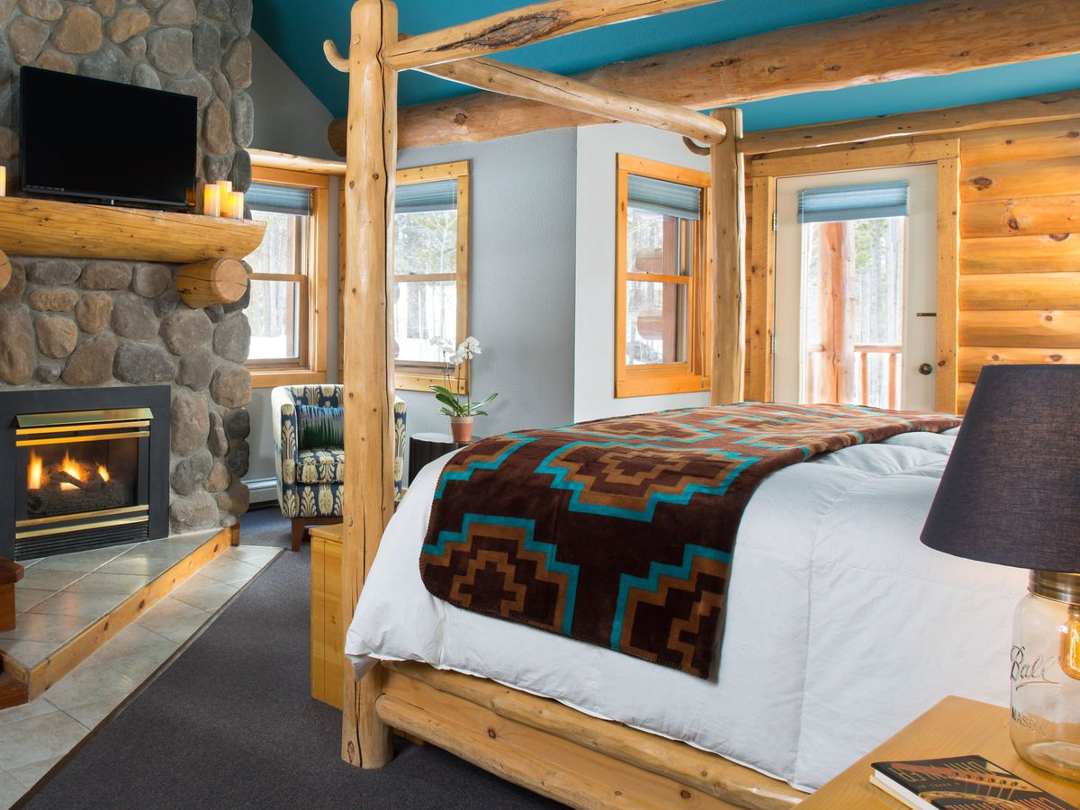 A four-post timber bed with white duvet and Navajo-print blanket sits in front of a stone fireplace.