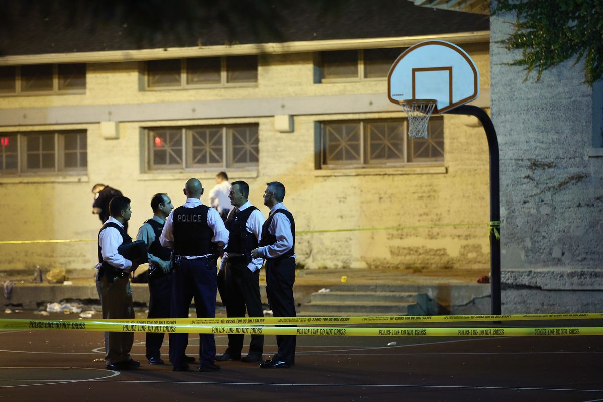 Chicago police talk in a basketball court, the scene of a shooting.