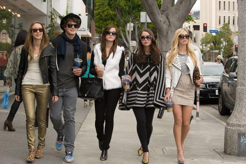 A row of well-dressed teenagers walk down the sidewalk.