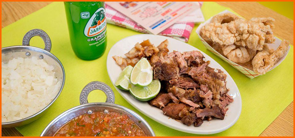 A plate of carnitas alongside chicharrones, salsa, onions, and a Jarritos beverage.