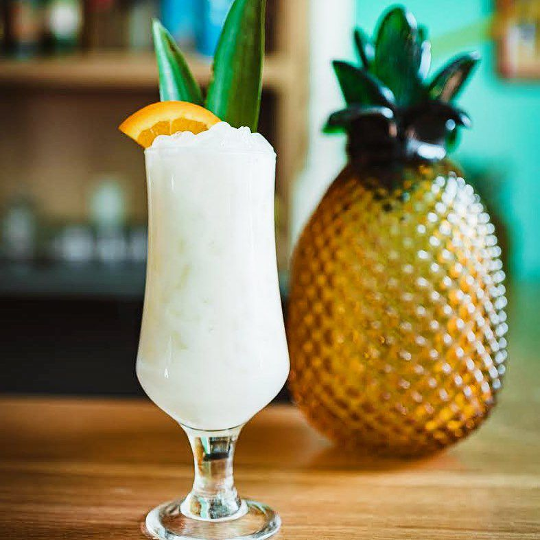 A slushy white pina colada sits in a tall glass, garnished with an orange slice and pineapple fronds. It sits next to a decorative metallic pineapple on a wooden bar.