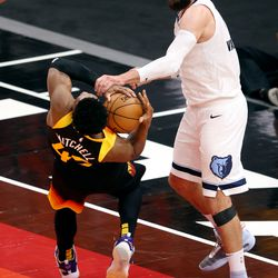 Utah Jazz guard Donovan Mitchell (45) falls as he struggles to hold the ball with Memphis Grizzlies center Jonas Valanciunas (17) as the Utah Jazz and Memphis Grizzlies play Game 2 of their NBA playoffs first round series at Vivint Arena in Salt Lake City on Wednesday, May 26, 2021. Utah won 141-129.