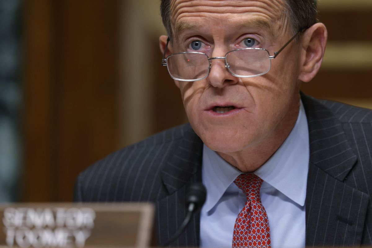 Toomey, rimless glasses perched on his nose, speaks into a microphone while in a dark pinstripe suit, pale blue shirt, and red tie.
