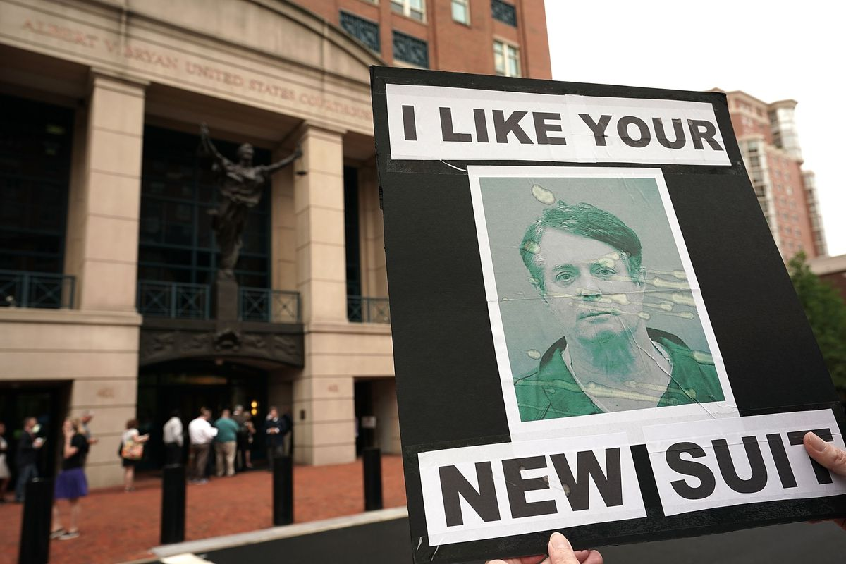 """A person holds a sign that says """"I like your new suit"""" and shows Manafort's mug shot."""