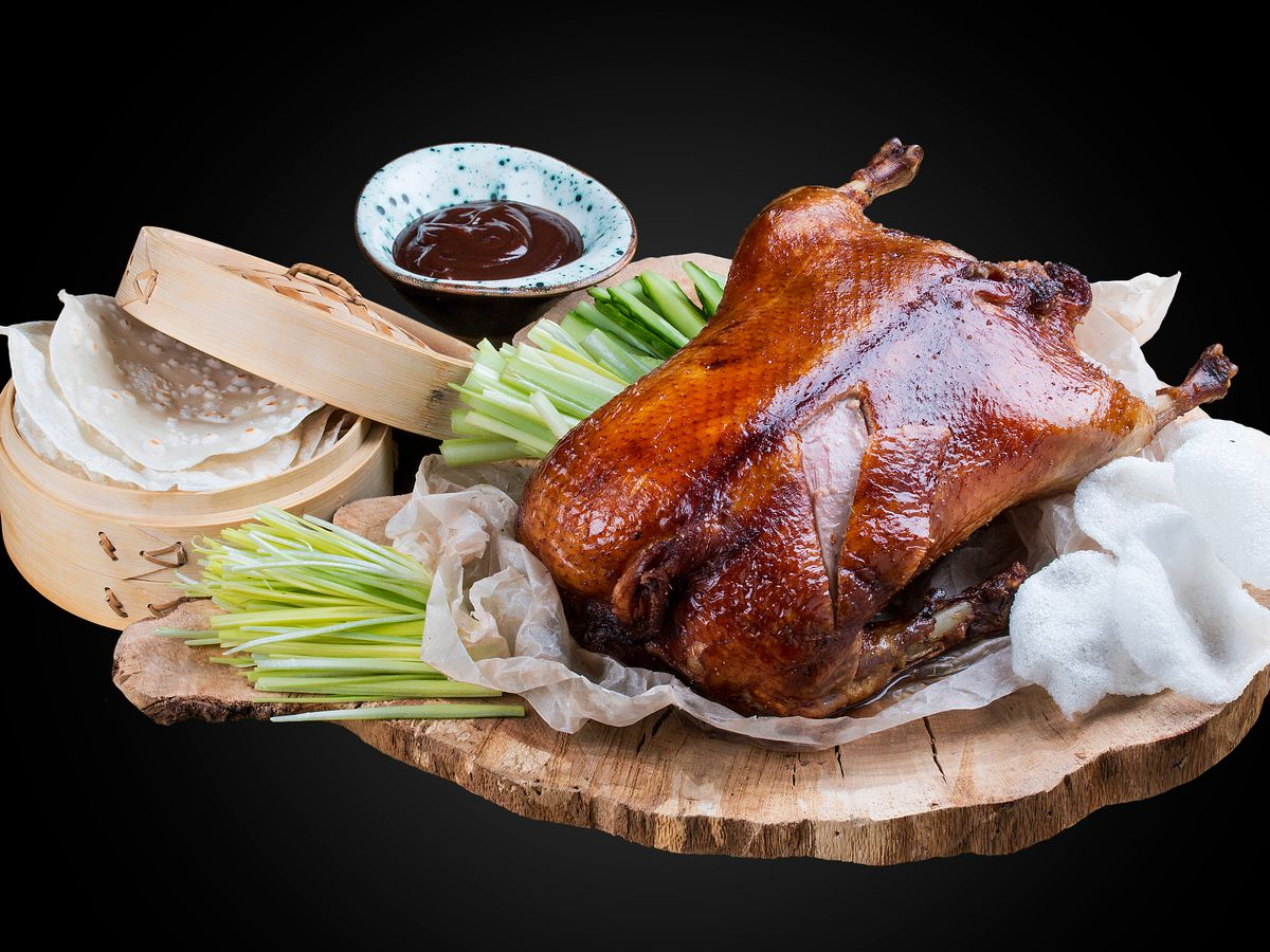 Peking duck with dipping sauce and other garnishes.