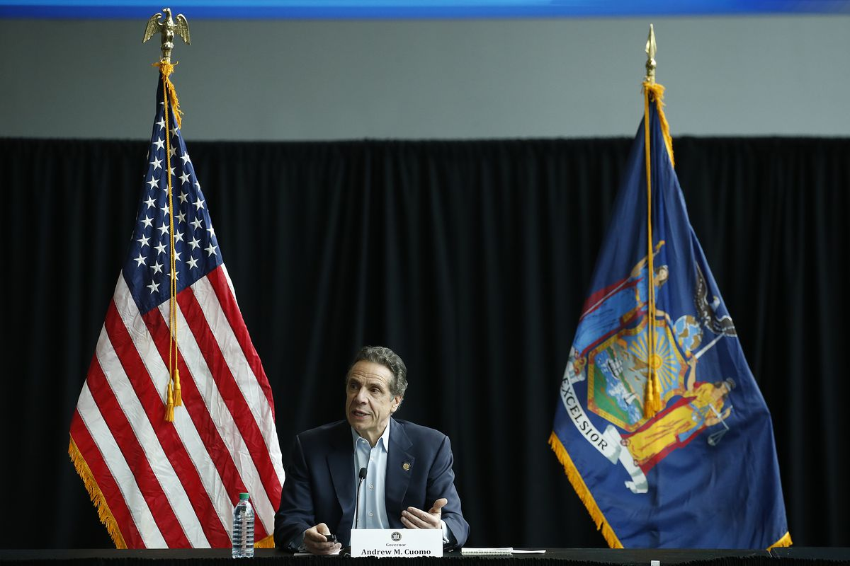 New York State Governor Andrew Cuomo sits in front of the state flag and U.S. flag at the Jacob Javits Center