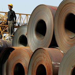 FILE - In this Nov. 18, 2004 file photo, a worker stands on a stack of rolled steel, shipped from the Baosteel factory in Shanghai destined for car manufacturers, on a dock in Guangzhou in south China's Guangdong province. China's biggest steelmaker Bapsteel Group said Thursday, Sept. 27, 2012 it has shut down a mill in Shanghai due to lack of demand in a new sign of weakening growth in the world's second-largest economy.