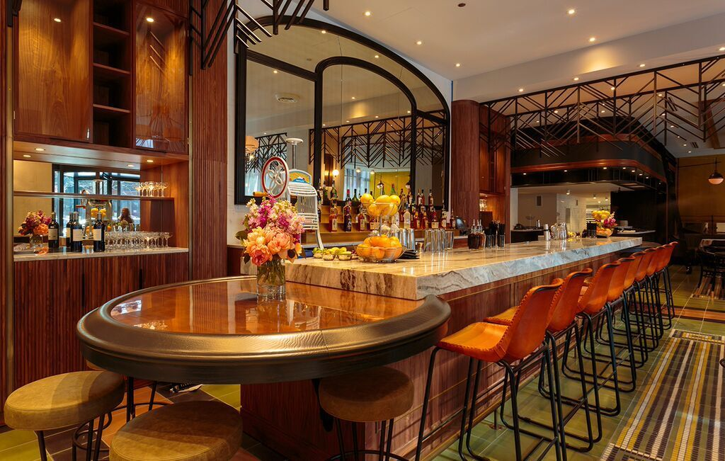A bar with dark woods, mirrors and leather chairs.