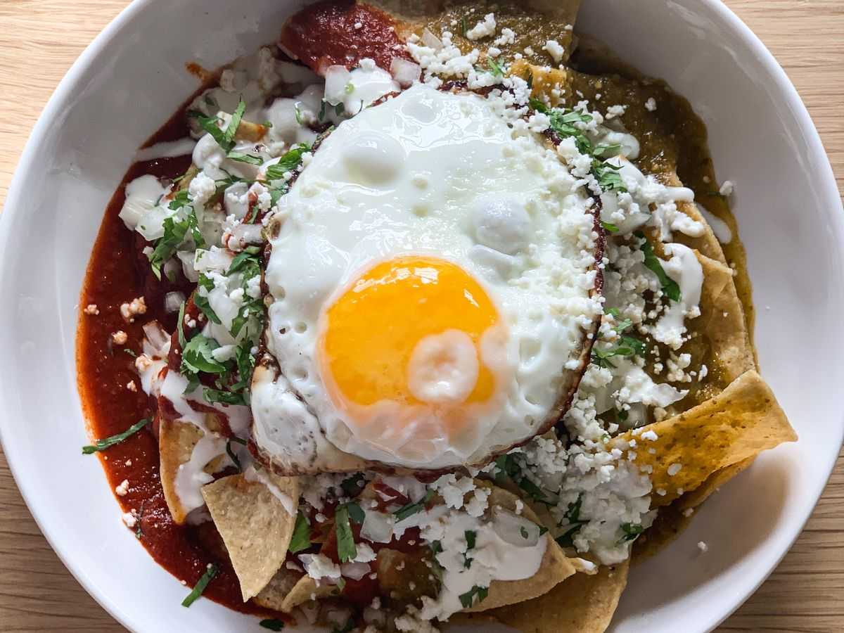 bowl with tortilla chips, cheese, red sauce, and egg