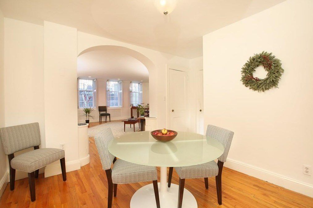 A dining room with a table and chairs and there's an archway leading to another room.