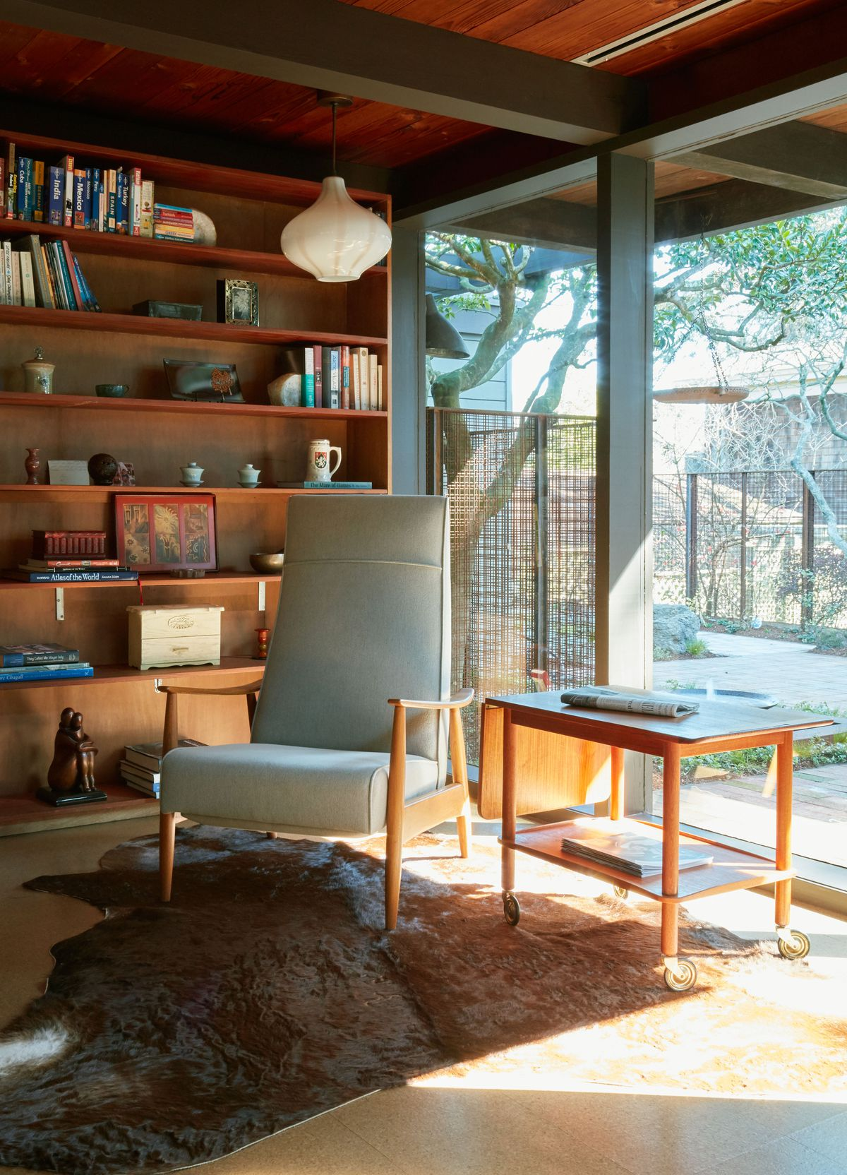 A living area. There is a chair and a table. There is an area rug. On the far wall are floor to ceiling shelves full of books and objects. On the other wall are floor to ceiling windows overlooking a yard.
