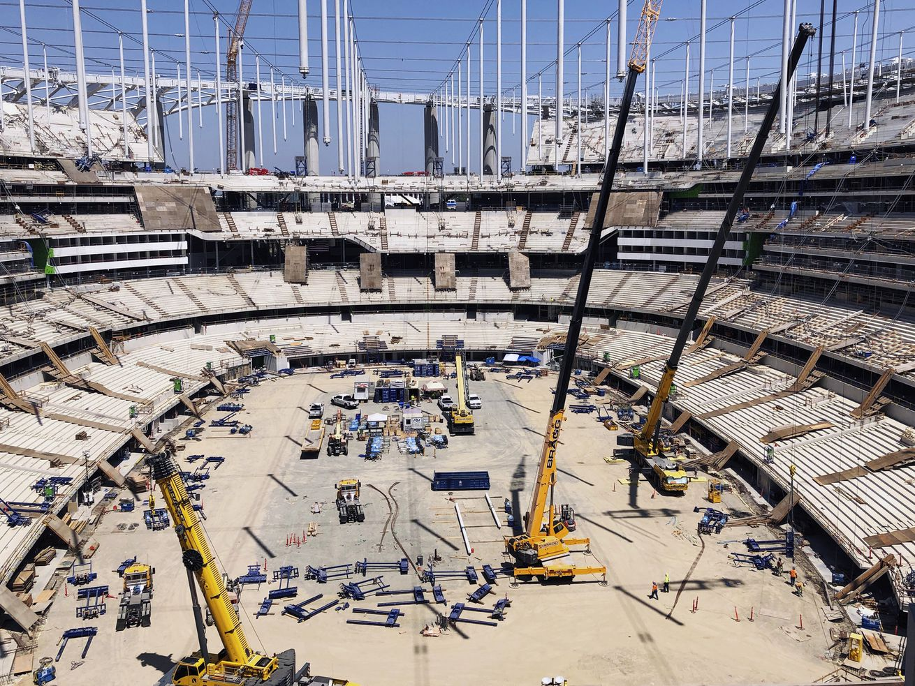 An aerial photo of an under-construction stadium, with a dirt floor and visible beams.