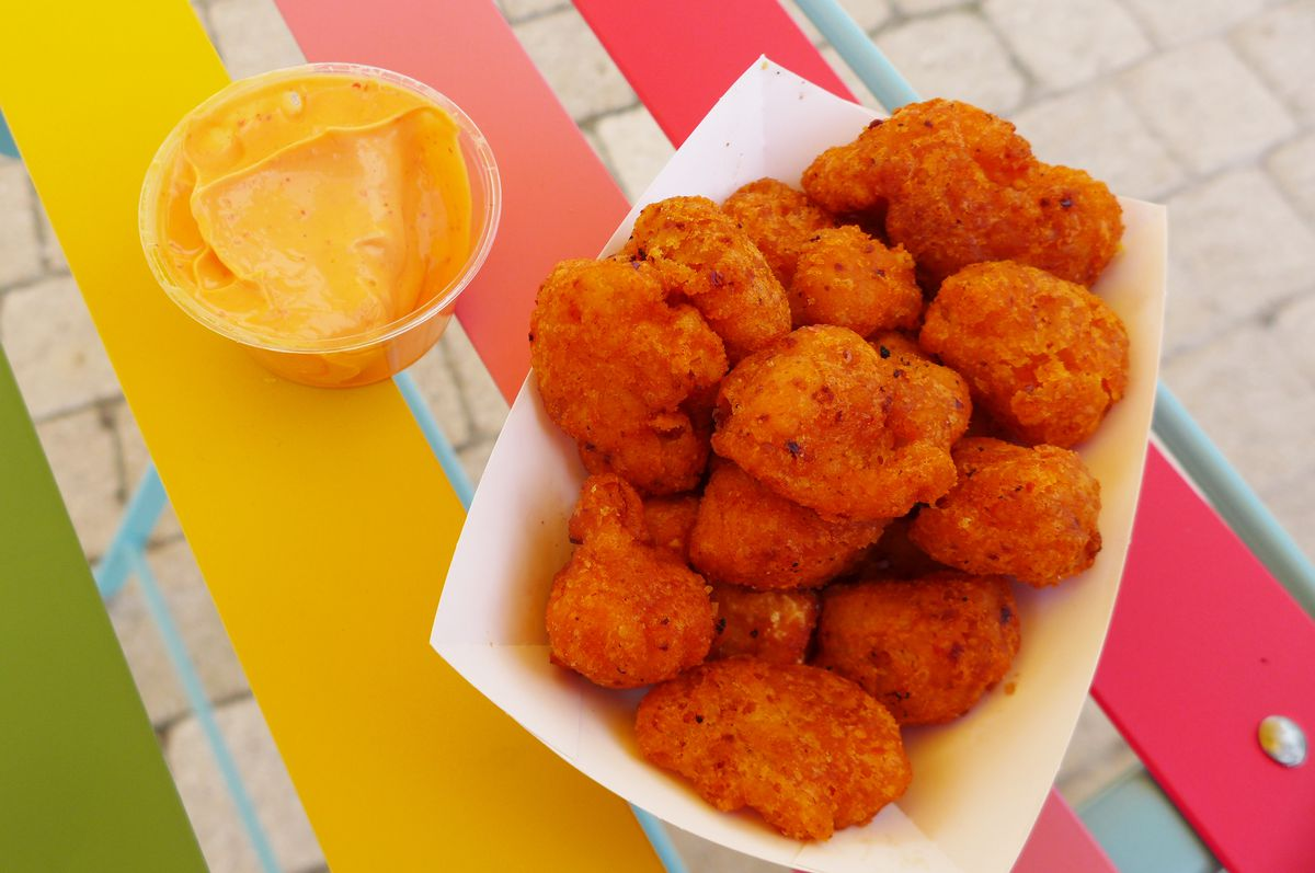 A basket of deep-fried florets, with a pinkish orange sauce on the side in a little cup.