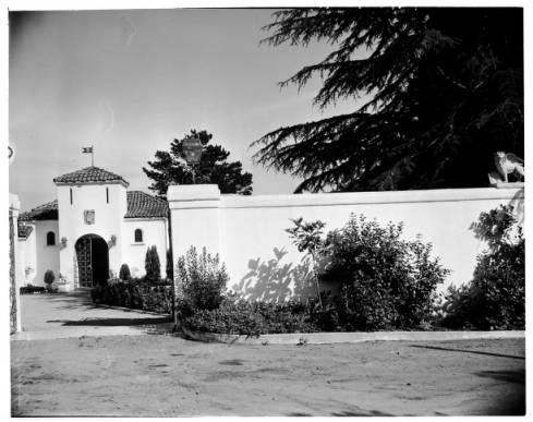 The exterior of a house. There is a large wall and a yard in front of the house. The house has a large entryway. There are trees and plants outside of the house.
