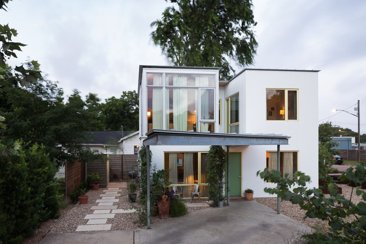 Two-story white house with adjacent separate wings, small, flat roofs, contemporary