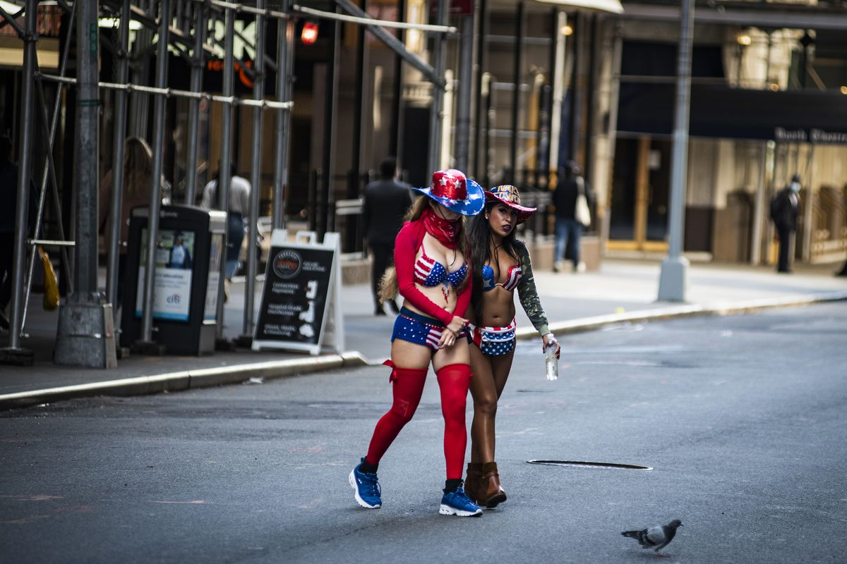 """Naked Cowgirl Patricia Burck (right) walks with another """"naked"""" she often works with in Times Square."""