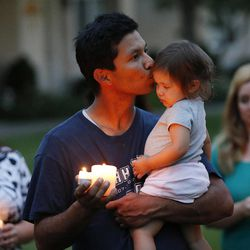 Eudaldo De Laguardia kisses his daughter Michiko as friends gather during a candle light vigil in Logan Thursday, July 10, 2014. Ronald Lee Haskell, a recent Logan resident, has been charged with multiple counts of capital murder in a shooting in Texas. Haskell and his family lived in Logan for several years.