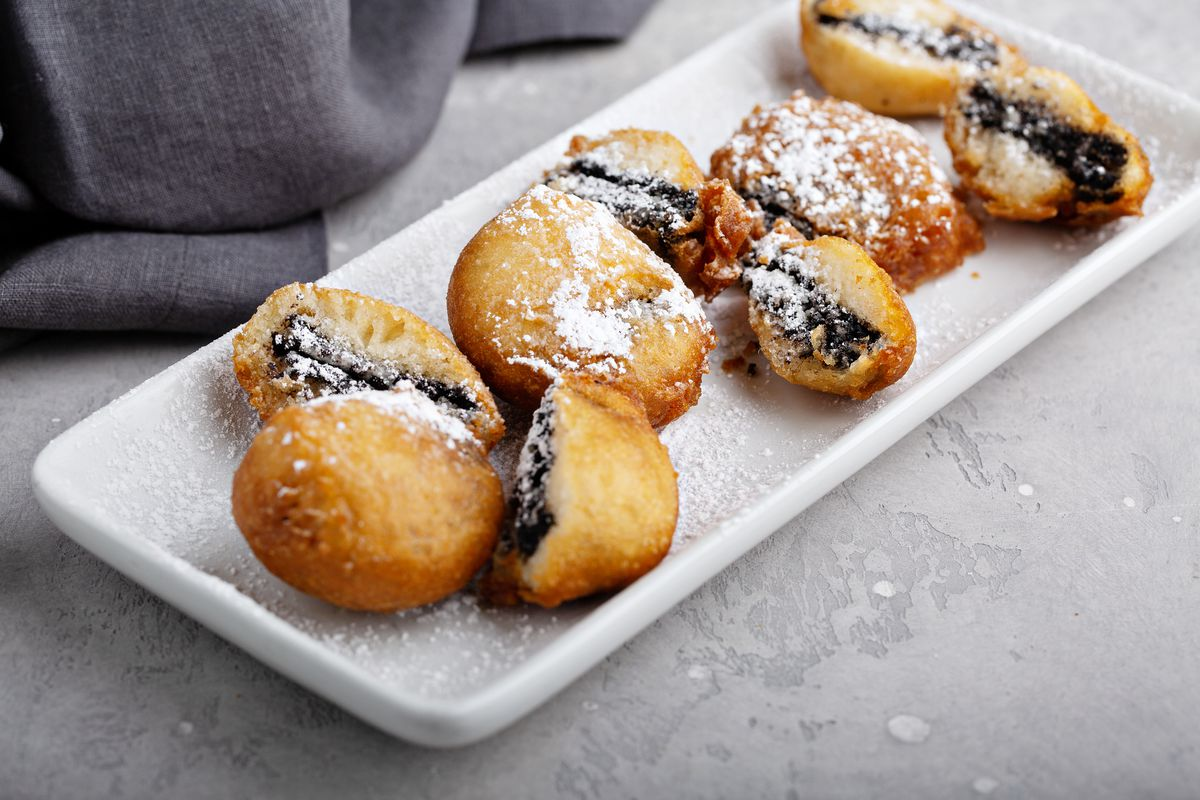 A white rectangular platter with deep-fried Oreos, some cut into quarters and halves sprinkled with powdered sugar
