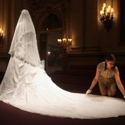 LONDON - JULY 20:   Caroline de Guitaut, curator of the exhibition display adjusts the Duchess of Cambridge's wedding dress, designed by Sarah Burton for Alexander McQueen, before it goes on exhibit at Buckingham Palace during the annual summer opening on