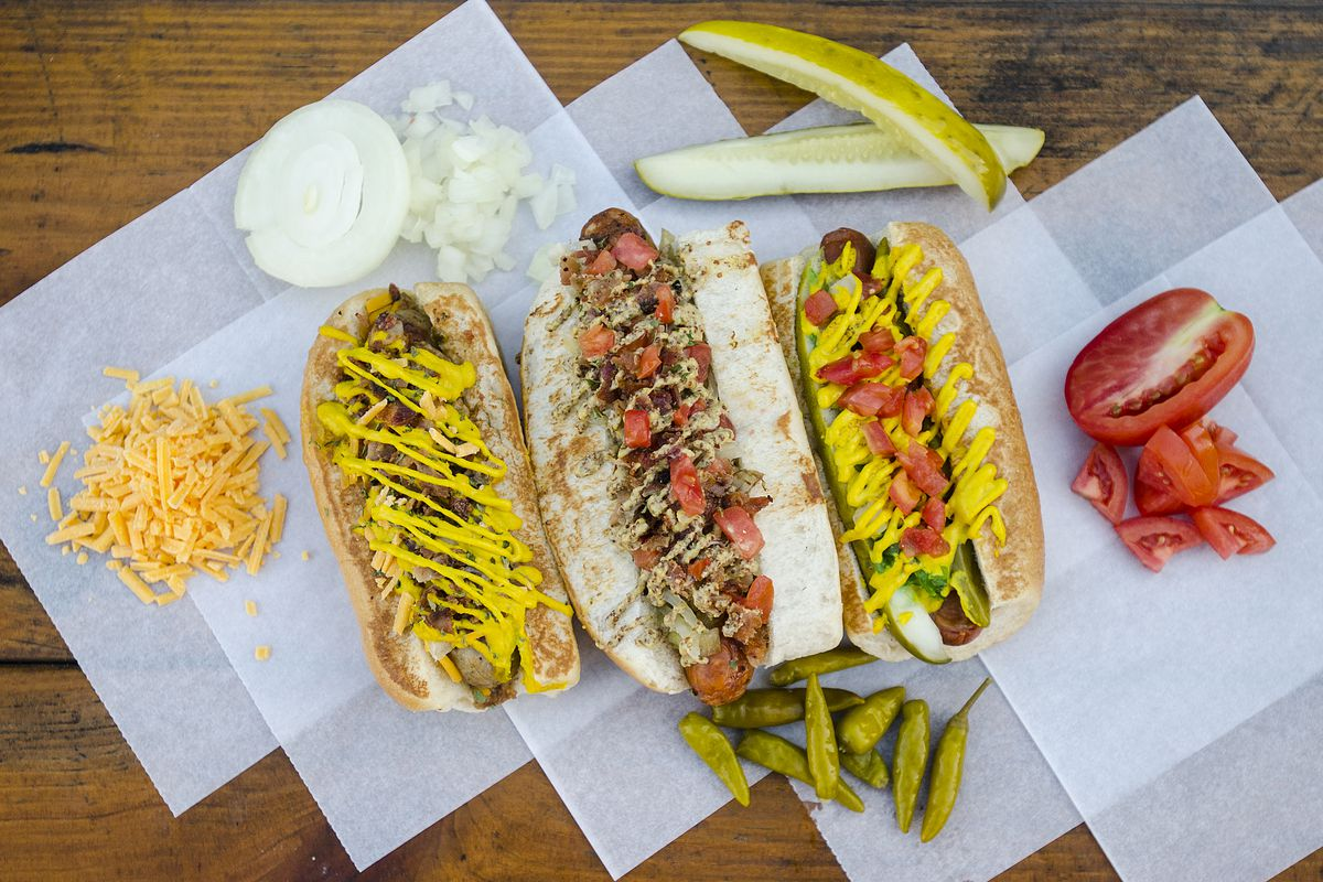 three gourmet hot dogs sit on paper on a wooden table surrounded by condiments like pickles, cheese, and peppers